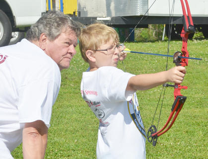 Gordon Walker of Mt. Roberts Baptist Church's On Target for Christ archery ministry helps his grandson, Will Taylor, 10, of Campbellsville take aim.