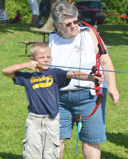 Roberta Walker of Mt. Roberts Baptist Church's On Target for Christ archery ministry helps Jackson Osbourn, 7, of Springfield set up his shot.