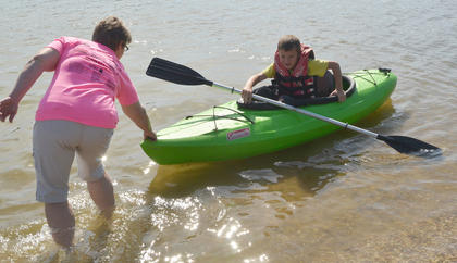 Susan Wise of Campbellsville helps Dylan Childress, 9, of Campbellsville, get in the water as he learns to use a kayak.