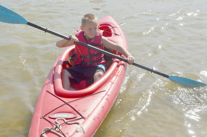 Harlee Thompson, 5, of Greensburg, learns to paddle a kayak.