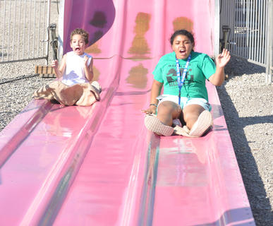 Brayden King, left, and Kaela King react as they finish the Fun Slide at the Taylor County Fair on Wednesday.