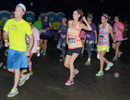 From left, Chad Shively, Stacie Lay and Rhonda Schnieder lead a dance after they finish the race.