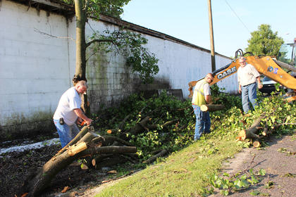 From left, Campbellsville Water & Sewer Co. employees Ronnie Murray, Kyle Young and David Revis clean up the remnants of a Bradford pear tree that was destroyed during Thursday morning's storm.
