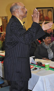The Rev. James I. Buford, who served as master of ceremony, claps in rhythm with the music at Saturday night's MLK reception.