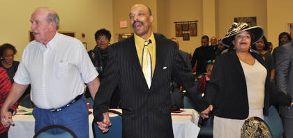"""Ronnie Allen, the Rev. James I. Buford and Minister Pamela Young Buford hold hands during the closing song """"We've Come This Far by Faith"""" at the MLK reception on Saturday night."""