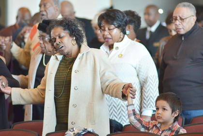 """Beverly Bridgewater and others hold hands and sing """"We Shall Overcome"""" to close Sunday's MLK worship service."""