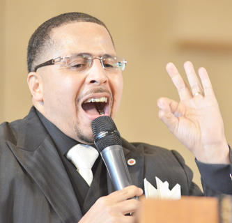 """The Rev. Walter Davis IV, pastor at First Baptist Church, spoke on Sunday and encouraged the crowd to not forget where they have come from. He encouraged people to think about how they interpret God and the place he has in their lives. """"How you answer these questions will determine how you treat the person sitting next to you."""" He encouraged the audience to see all people as God's creations."""