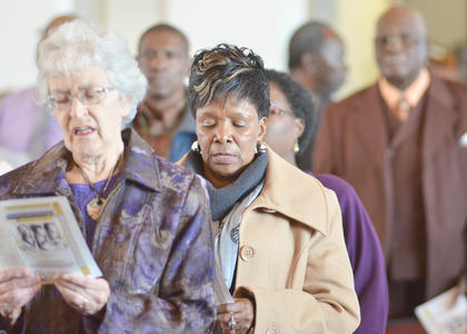"""Community members sing along to """"Lift Every Voice and Sing,"""" which congregation members sang to open Sunday's MLK worship service."""