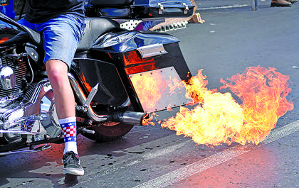 Fire shoots out from the exhaust pipe of a motorcycle in Thursday's parade.