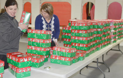 Tracy Gaskins Thomas, at left, and Jennifer Lauer, sort through OCC shoeboxes.