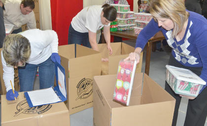 Volunteers pack OCC shoeboxes into cardboard boxes.