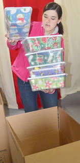 Grace Arnold packs OCC shoeboxes into a cardboard box.