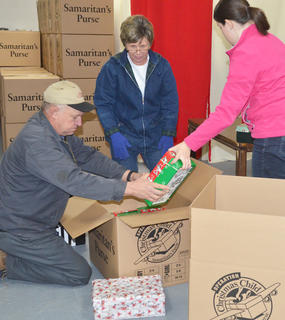 From left, Ronnie and Brenda Patton and Grace Arnold sort OCC shoeboxes to be taken to Boone, N.C., before being shipped worldwide.