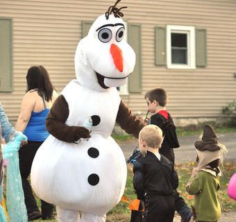 """A resident dressed as Olaf from the Disney movie """"Frozen"""" greets a trick or treater Tuesday night."""