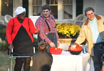 Jenna Gardner, left, Brandon Rainwater and Jacob Rainwater hand out candy to trick or treaters Tuesday night.