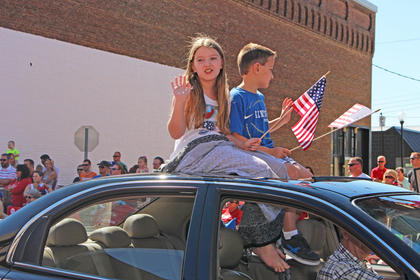 Children smile and wave the American Flag while riding on the roof of a car.