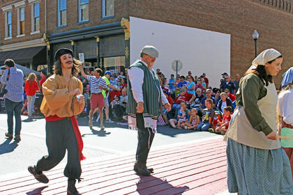 """Actors in """"Fiddler on the Roof,"""" presented by Campbellsville University and Town Hall Productions, display their abilities to the crowd as they walk by."""