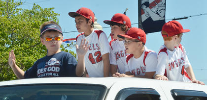 Members of the Angels baseball team ride atop a truck in the Fourth of July parade on Friday morning.