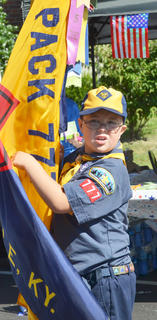 Daniel Caton of Campbellsville, a member of Cub Scout Pack 777, carries his pack's flag during the Fourth of July parade on Friday morning.