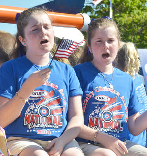 Members of the national champion Kentucky Christian Academy archery team road in the July Fourth parade on Friday morning.