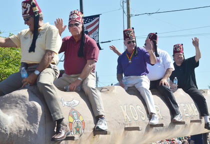 Kosair Shriners club members wave to the crowd during the Fourth of July parade on Friday morning.