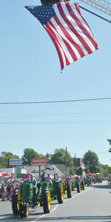 Residents drive tractors down Main Street during the Fourth of July parade while Campbellsville Fire & Rescue's large American flag waves above them.
