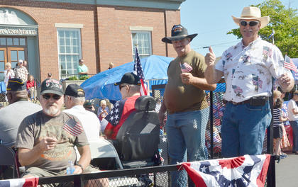Veterans ride and wave to spectators in the Fourth of July parade on Friday morning.