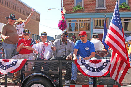Veterans ride atop a float in the parade.