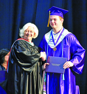 Pat Hall, Campbellsville Independent School board member, presents Josh Dooley with his diploma.