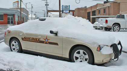A Taylor County Sheriff's Office cruiser sits near the Taylor County Courthouse, covered in snow.