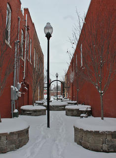The alley off of Main Street is covered in snow.