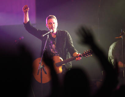 """A packed house of about 850 people attended a concert at Living Grace Church Friday night. The show, which was part of the """"Hands of God"""" tour, featured Christian artists Jon Bauer, All Things New, Sanctus Real and Francesca Battistelli. Here, Matt Hammitt, lead singer of Sanctus Real, raises his hand during a performance of the song """"Pray,"""" and members of the audience do the same."""
