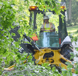 Charles Thompson of Atmos Energy uses a backhoe to remove trees that blocked the entrance to the Forest Hills Subdivision.
