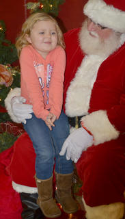 Kamber Beckley, 5, thinks about what she wants for Christmas as she sits in Santa's lap.