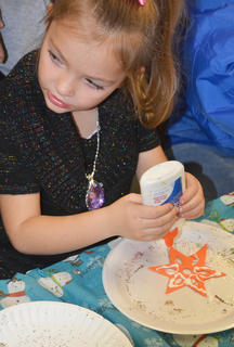 Kimberly Prebee, 4, a preschool student, glues her Christmas ornament before sprinkling it with glitter.