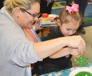 Kimberly Prebee, 4, a TCES preschool student, gets some help from her mother, Maria, to put the finishing touches on her glittery Christmas ornament.