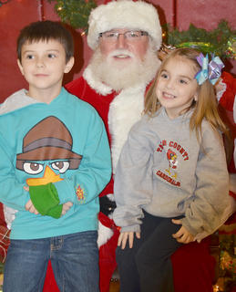 Aiden Satterly, 9, at left, a fourth-grader at TCES, and his sister, Kadee, 5, a kindergartener, smile with Santa.