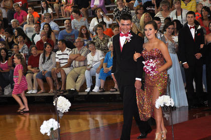 Anthony Hillard holds Brooklyn Ferrell's sparkling dress as they walk down the runway at TCHS prom.