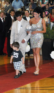 Tanner Ford and Zoe Lockard smile as her younger brother Brody joins them on the TCHS prom runway.