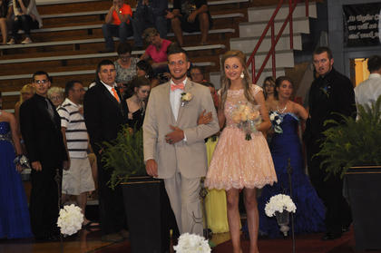 Mckayla Cash and Mark Harris smile as they walk down the runway during TCHS prom walk-in.