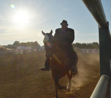 The crowd can only see Anthony Curry of Greensburg's silhouette as he participates in this year's Tommie Johns Memorial Championship Horse show at the fair on Saturday.
