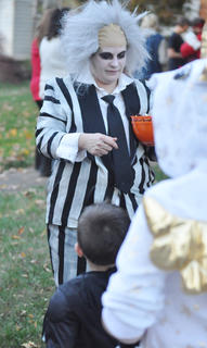 Tori Settles, dressed as Beetlejuice, hands out cany to trick or treaters Tuesday night.
