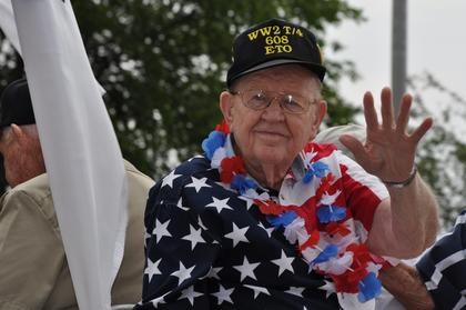 Veteran Lynwood Kessler waves from a float during the July Fourth parade downtown.