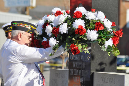 The American Legion puts flowers on the war memorial.