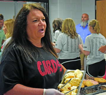 Volunteer Sherry Henderson stocks the buffet with more biscuits.